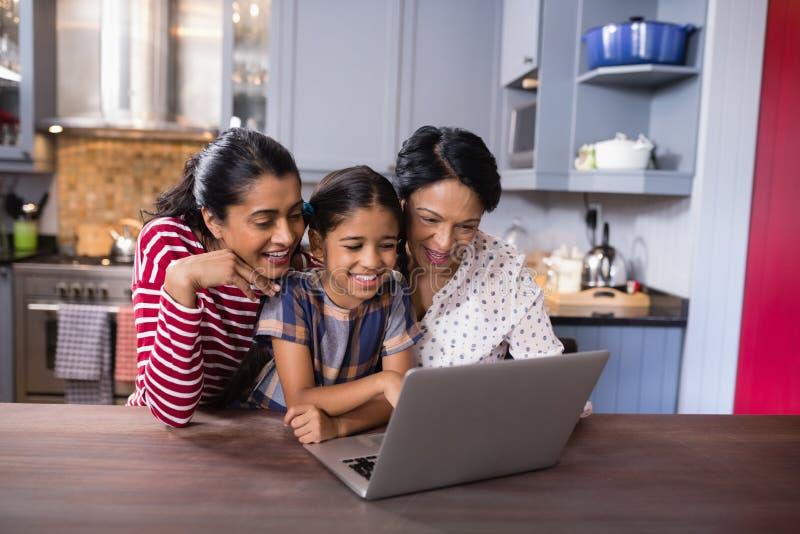 Le denutveckling familjen som använder bärbara datorn i kök arkivbild