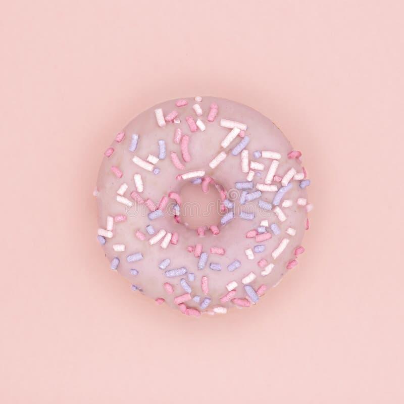 Le dessert doux de beignet avec coloré arrose la configuration plate sur le fond de papier de corail en pastel Concept minimal de photos stock