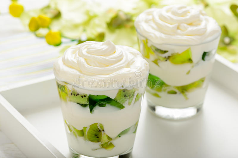 Le dessert sain de yaourt avec des kiwis, gélifient et écrèment en verre photographie stock