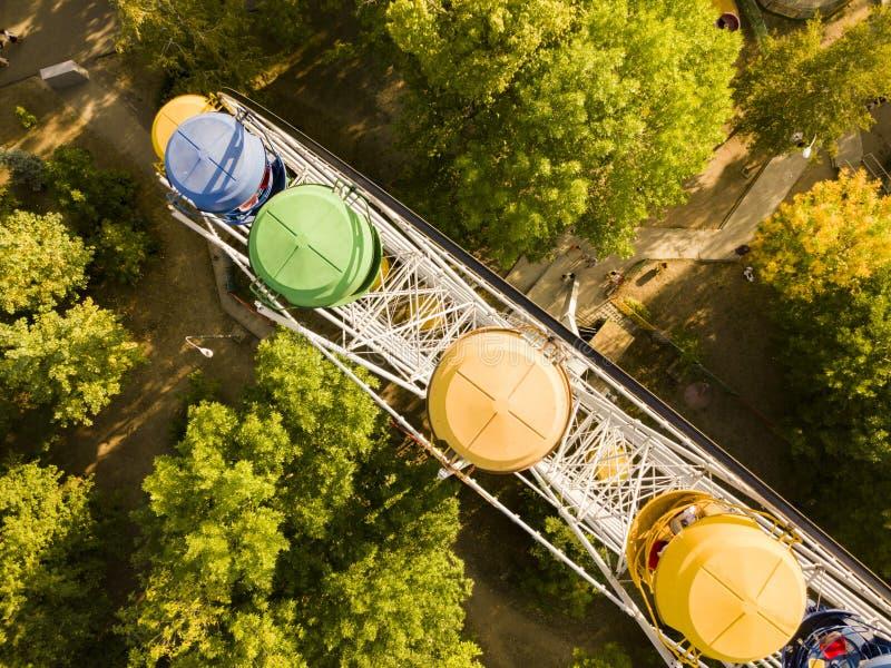 Le dessus aérien directement au-dessus de la vue des ferris roulent dedans le parc public de ville d'amusement d'été, le tir d de photos stock