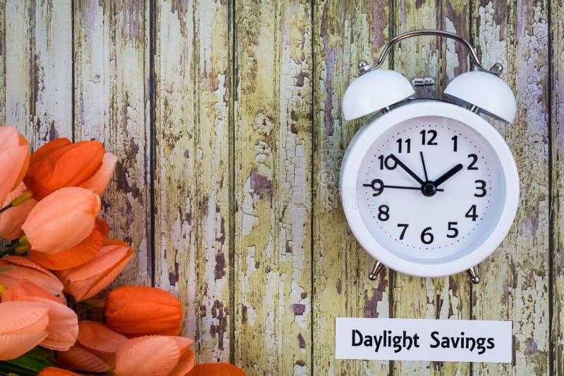 Le dessus de concept de ressort de temps heures d'été regardent vers le bas avec l'horloge blanche et les tulipes oranges photos libres de droits