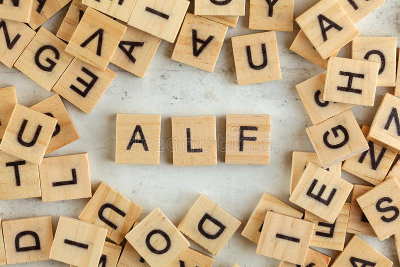 Le dessus en bas de la vue, pile des blocs en bois carrés avec ALF de lettres représente toujours pour écouter d'abord sur le con photo libre de droits