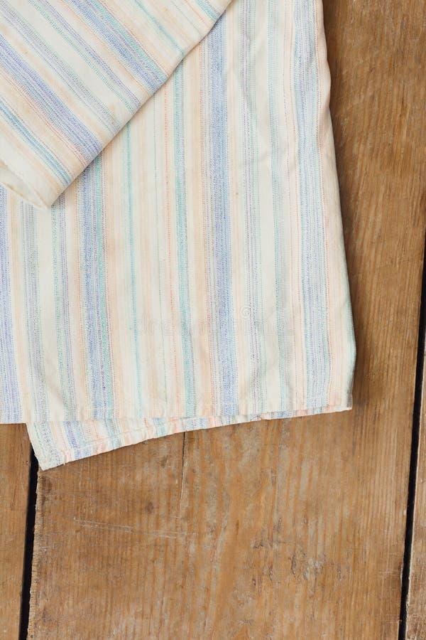 Le dessus en bois rustique de table de cuisine de serviette rayée blanche de cuisine luttent photo libre de droits