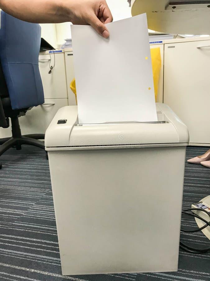 Le destructeur de papier d'utilisation d'homme d'affaires pour le retrait confidentiel de documents d'entreprise photo libre de droits