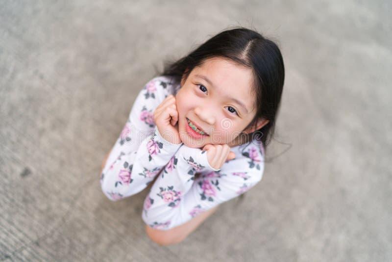 Le det asiatiska barnet med hänglsen på tänder royaltyfria foton