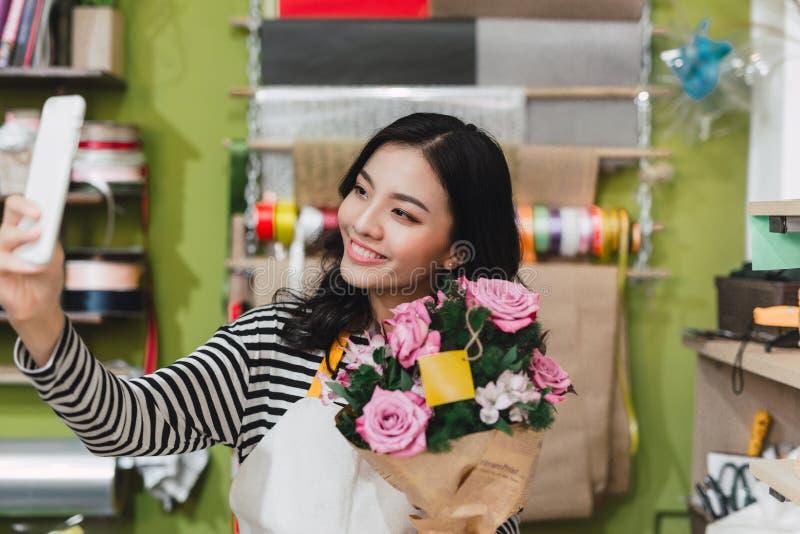 Le det asiatiska kvinnliga fotoet för blomsterhandlaredanandeselfie med buketten av arkivfoto