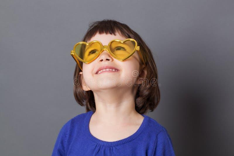 Le det förskole- barnet som bär gula hjärta-Shape exponeringsglas arkivbild