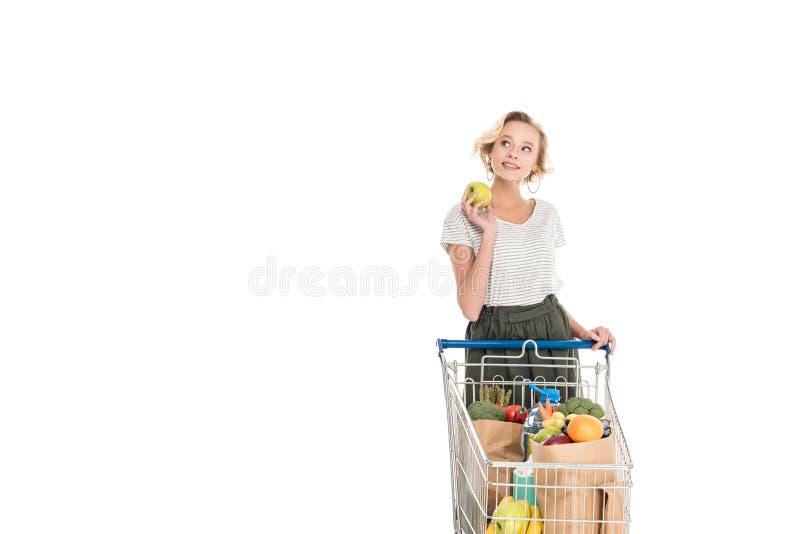 le det hållande äpplet för ung kvinna och se bort, medan stå med att shoppa spårvagnen med livsmedelsbutikpåsar royaltyfria bilder