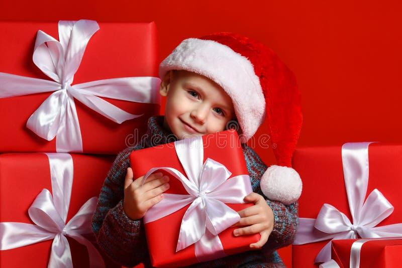 Le det roliga barnet i gåva för jul för röd hatt för jultomten hållande i hand Julfilial och klockor arkivfoton