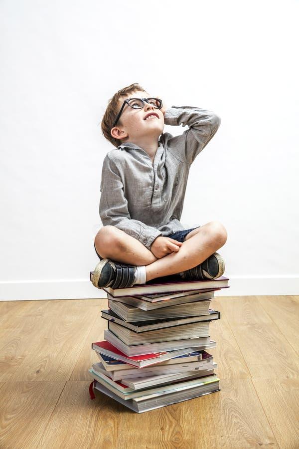 Le det smarta barnet som överst placeras av böcker för kultur arkivbilder
