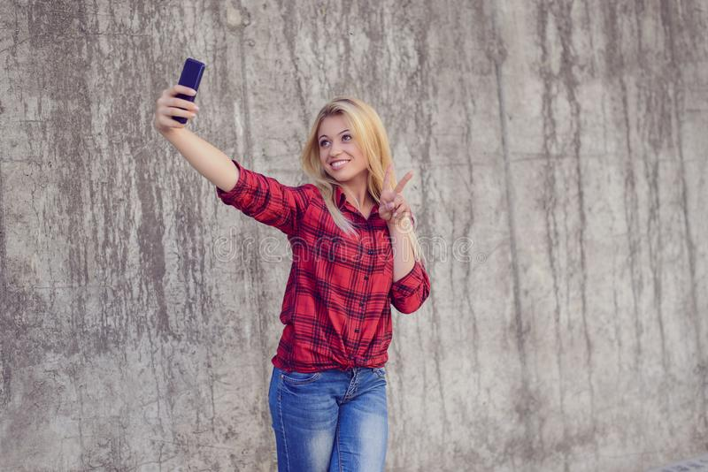 Le det taling självporträttet för lycklig kvinna genom att använda hennes mobiltelefon arkivbilder