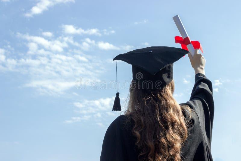 Le diplômé a mis ses mains et célébrant avec le certificat dans sa main et sentant ainsi le bonheur dans le jour de commencement  photo stock