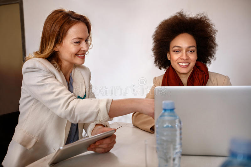 Le directeur avec l'employé font la consultation au sujet des affaires sur l'ordinateur portable photos libres de droits