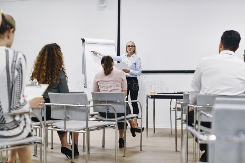 Le directeur donne une présentation aux employés dans une salle de séminaire image stock