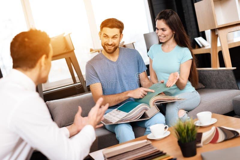 Le directeur et les acheteurs de magasin de meubles considèrent des exemples de couverture de meubles images libres de droits