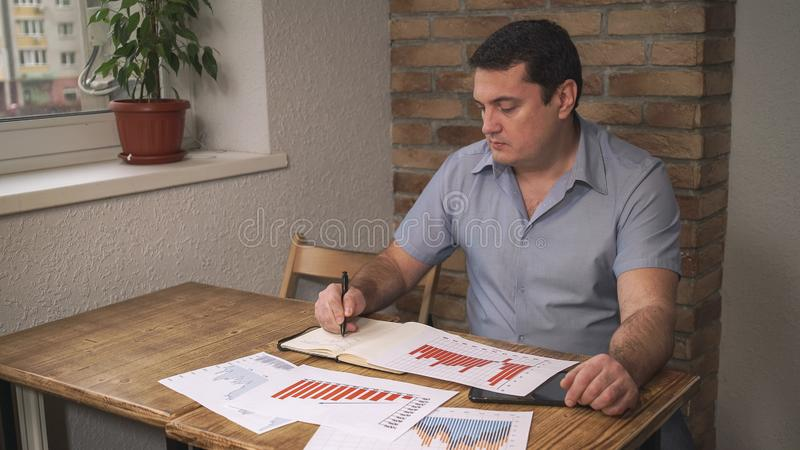 Le directeur examine les données de ventes pour assurer le mois, sont sur la table les documents image stock