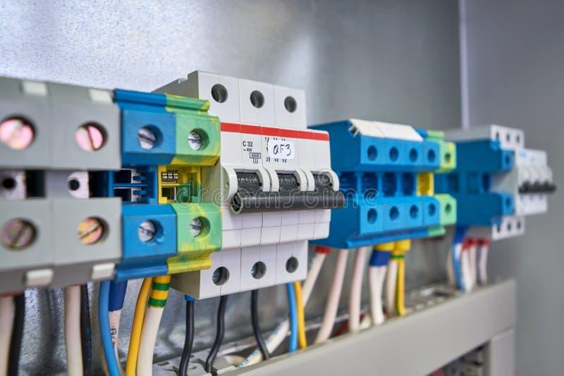 Le disjoncteur triphasé est installé dans la même rangée que les bornes de connexion dans le coffret électrique image stock