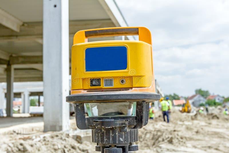 Le dispositif moderne fait des mesures avec l'outil rouge de niveau de laser photos libres de droits
