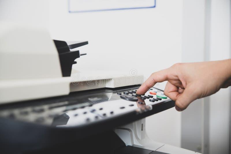 Le dispositif multifonctionnel au centre de bureau, travailleur place les options de balayage pour envoient la copie numérique de images libres de droits