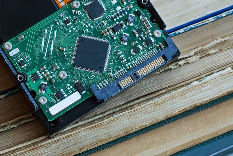 Le disque dur d'ordinateur se trouve sur le fond de livres photo libre de droits