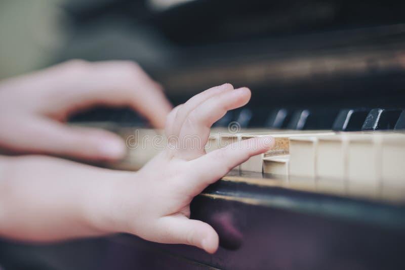 Le dita del ` s del bambino hanno messo sopra le chiavi del piano immagini stock