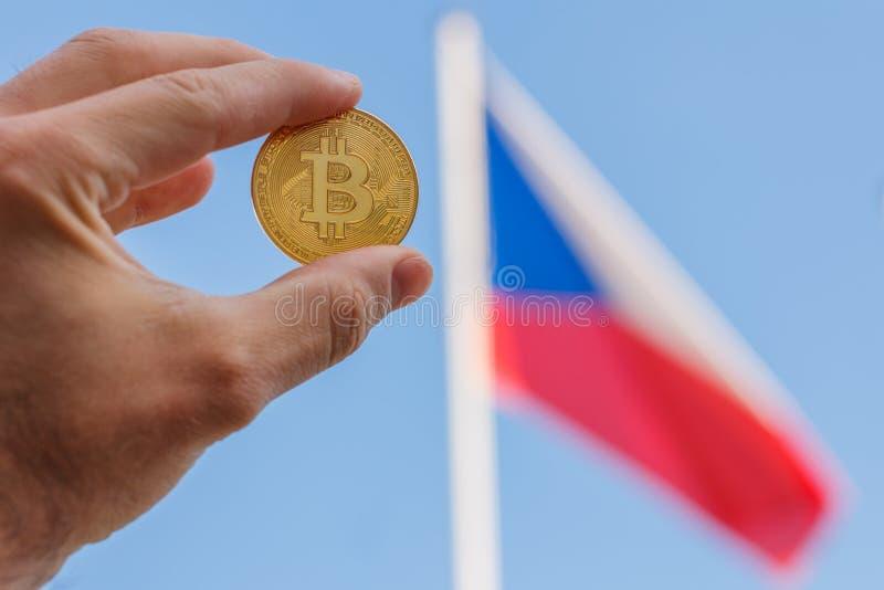 Le dita di un uomo stanno tenendo una grande moneta dorata di bitcoin davanti alla bandiera ed al cielo blu della repubblica Ceca fotografia stock libera da diritti
