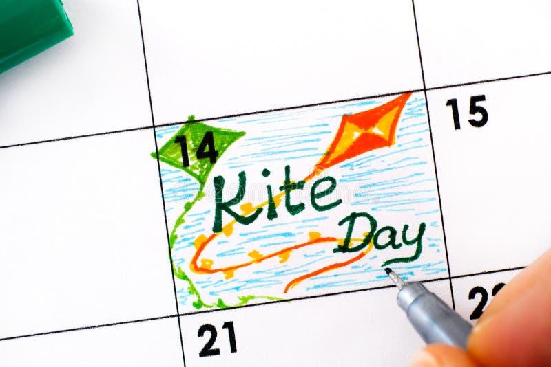 Le dita di una donna con penna ricordano Kite Day sul calendario fotografia stock libera da diritti