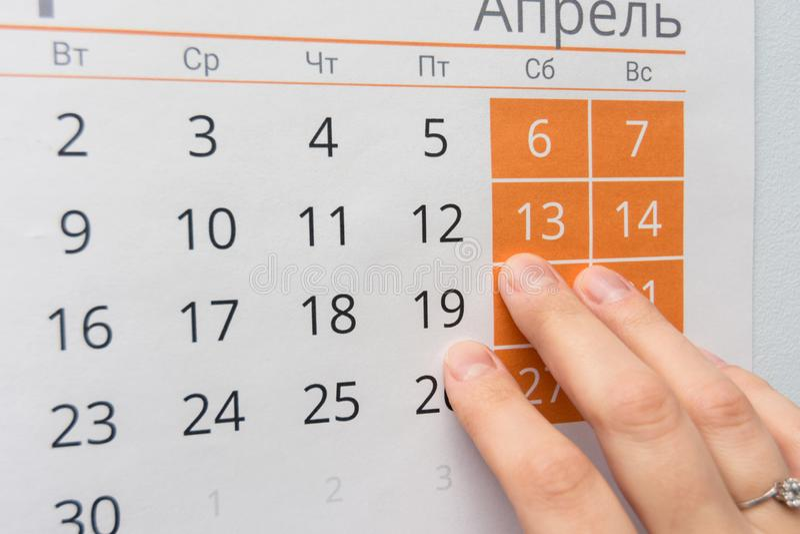 Le dita indicano il fine settimana nel calendario murale immagine stock libera da diritti
