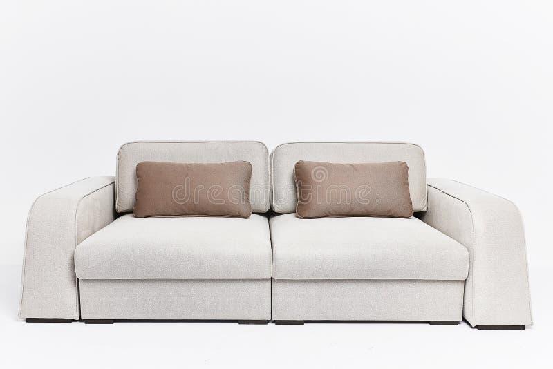 Le divan beige dans le style moderne avec deux oreillers bruns d'isolement sur le fond blanc photo stock