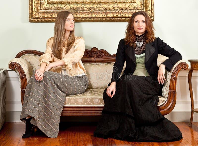 Le divan victorien de femmes se reposent images libres de droits