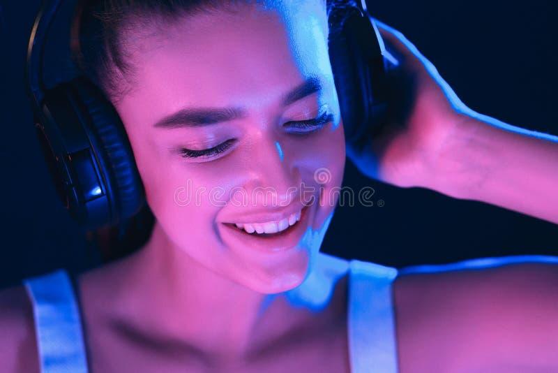 Le DJ dans le club Femme dans le casque illuminé par les lampes au néon photo stock