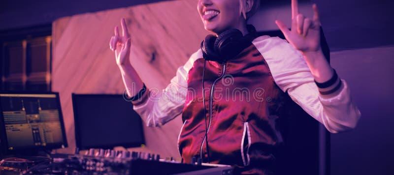 Le DJ féminin ayant l'amusement tout en jouant la musique dans la barre photographie stock libre de droits