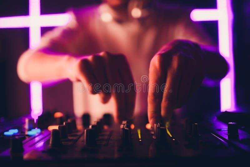 Le DJ jouant la musique au mélangeur sur le fond brouillé coloré photos libres de droits