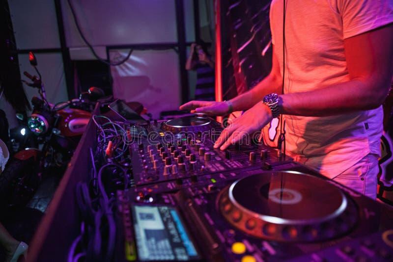 Le DJ jouant la musique au mélangeur sur le fond brouillé coloré photo libre de droits