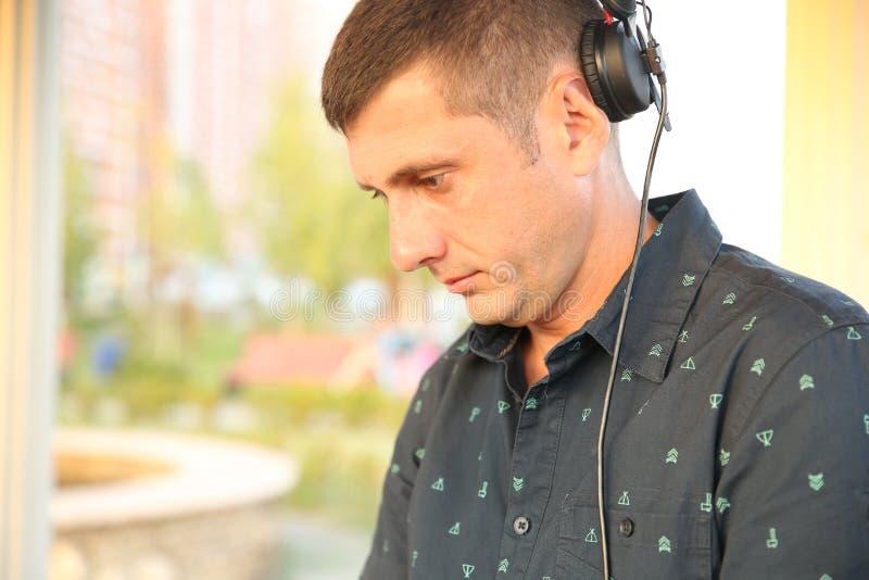 Le DJ joue la musique avec l'écouteur image libre de droits