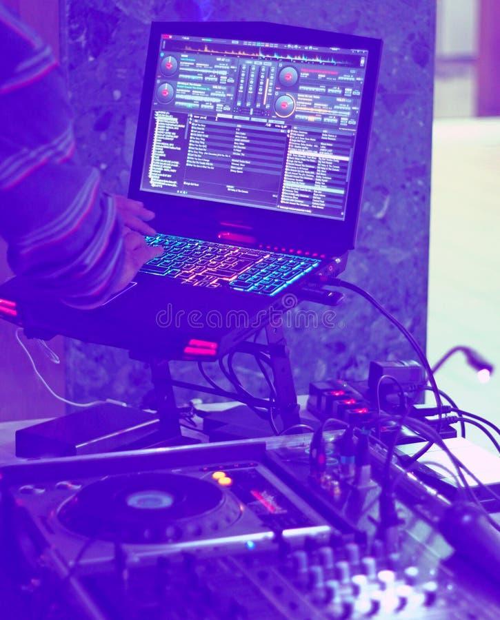 Le DJ se tiennent avec l'ordinateur portable à la partie image stock