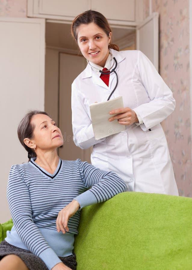 Le docteur amical demande au patient mûr se sent images stock