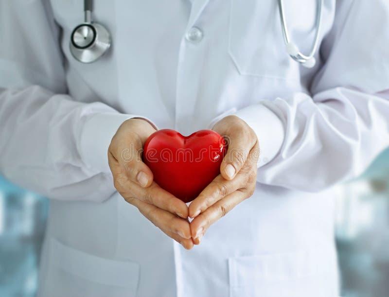 Le docteur avec le stéthoscope et le coeur rouge forment dans des mains sur l'hôpital photos stock