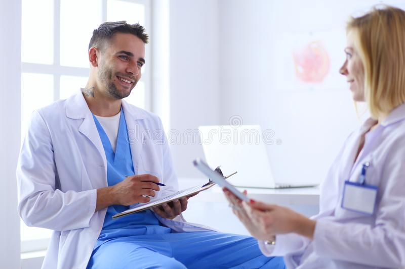 Le docteur beau parle avec le jeune patient féminin et fait des notes tout en se reposant dans son bureau photo stock