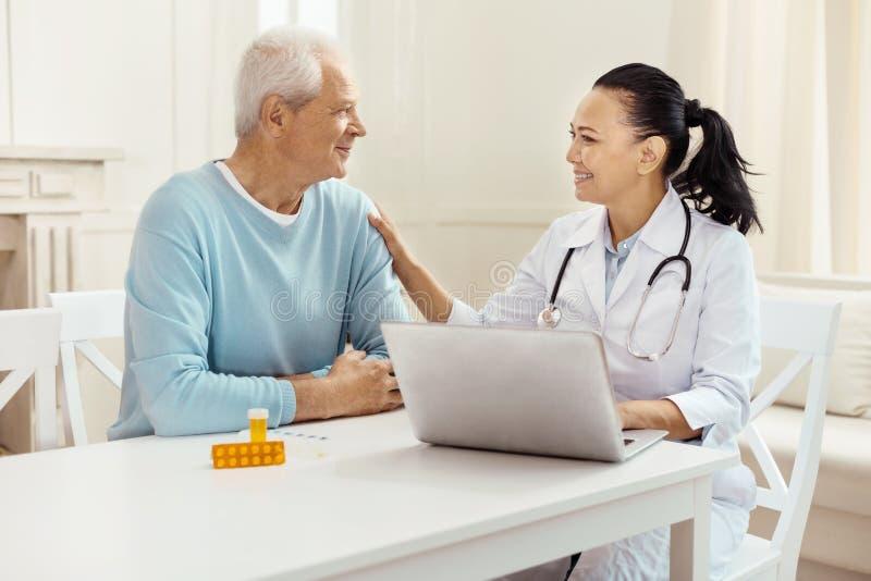 Le docteur bien disposé amical mettant sa main sur les patients épaulent image stock
