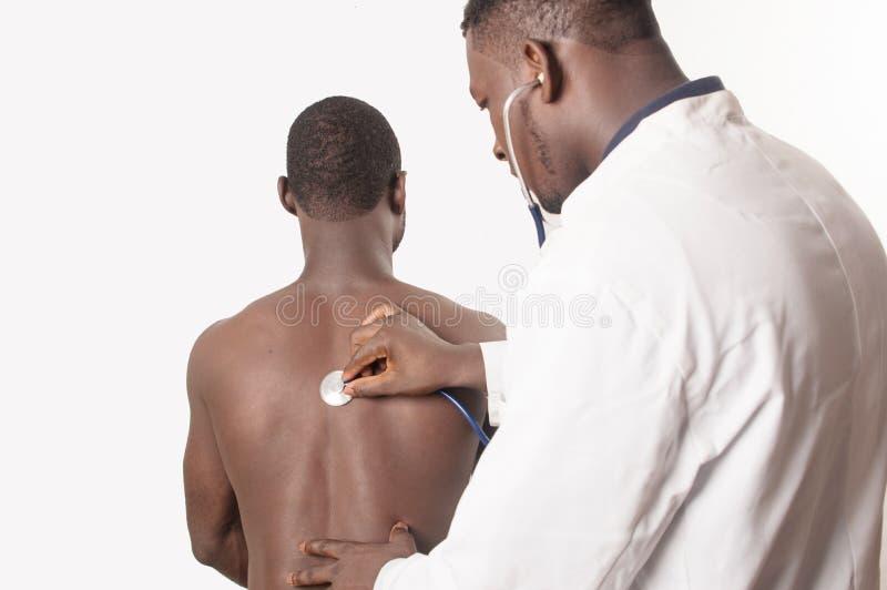 Le docteur consulte le patient avec un stéthoscope dans le dos photographie stock