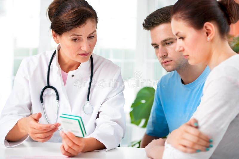 Le docteur consulte un jeune couple images stock