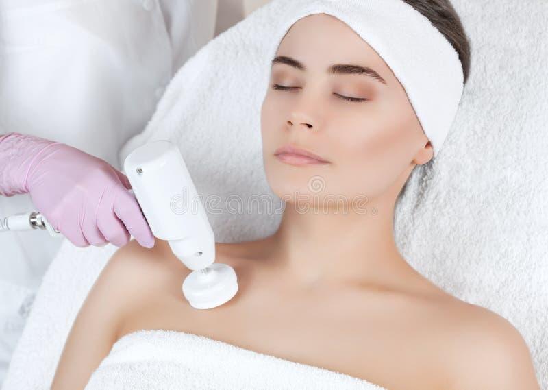 Le docteur-cosmetologist fait à l'appareil une procédure du nettoyage decollete de visage de matériel avec une brosse tournante m photos stock