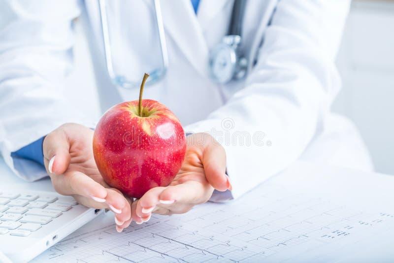 Le docteur de femme dans l'ambulance tient la pomme rouge dans des mains Sur l'ordinateur portable de bureau et le diagramme d'él image libre de droits