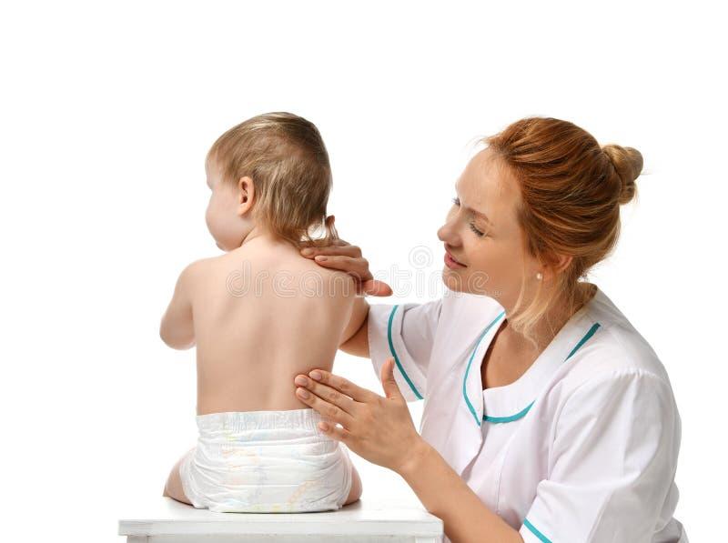 Le docteur de femme de pédiatre dans l'uniforme médical font le massage d'épine à une composition patiente en plan rapproché de p photographie stock libre de droits