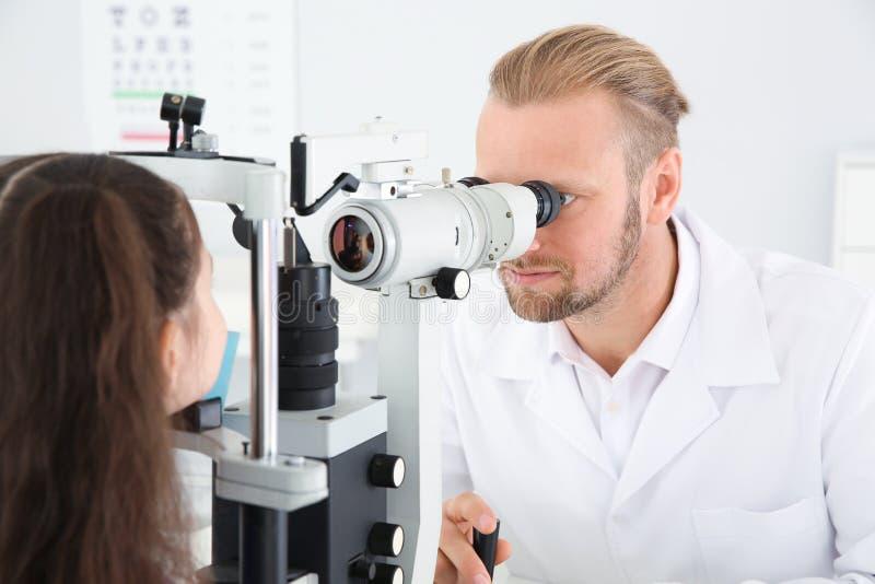 Le docteur des enfants examinant la petite fille avec l'équipement ophtalmique photographie stock libre de droits