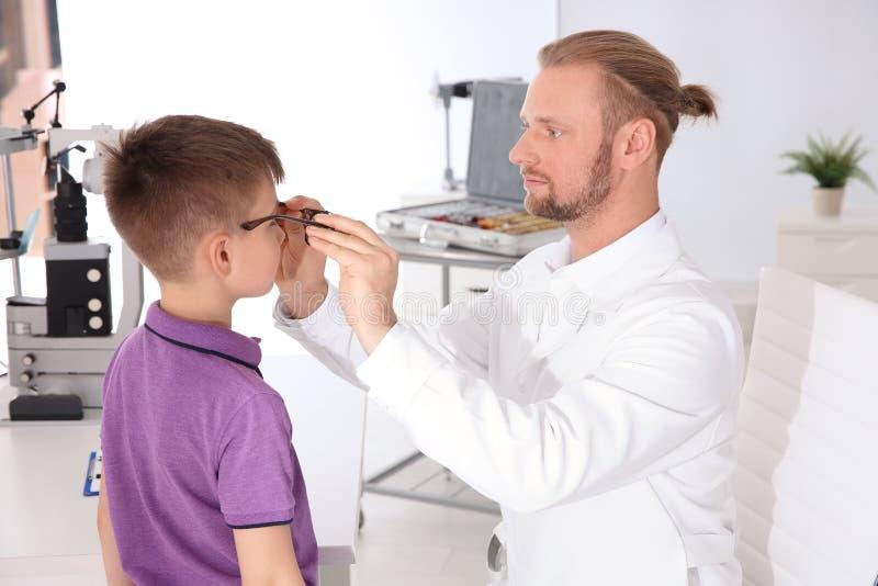 Le docteur des enfants mettant des verres sur peu de garçon photographie stock