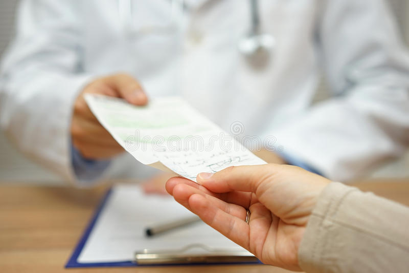 Le docteur donne une prescription à un patient féminin photographie stock