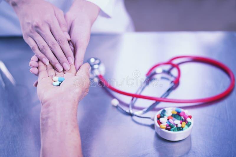 Le docteur donnent la médecine au patient, prenant soin du peop plus âgé image libre de droits