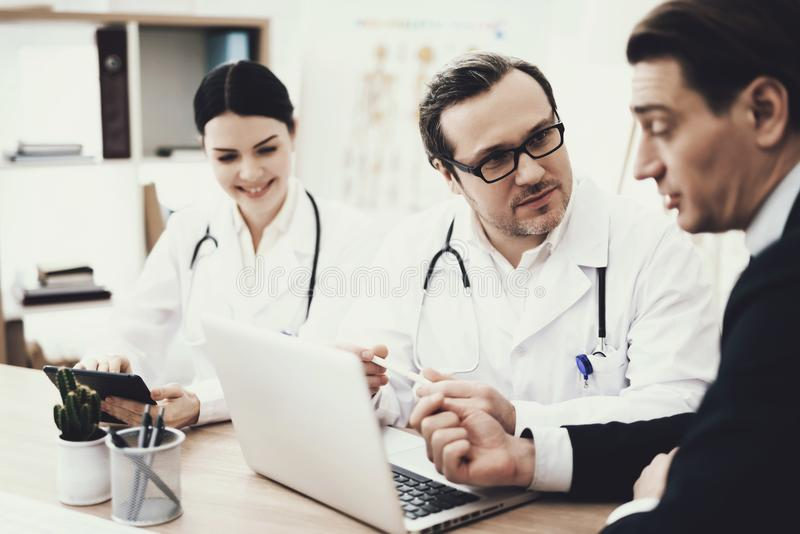 Le docteur en verres conseille le patient s'asseyant à la table avec l'ordinateur portable dans le bureau médical photo stock